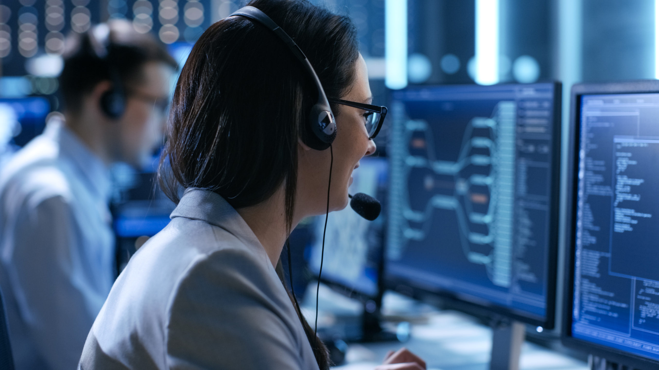 In the System Control Center Woman working in a Technical Support Team Gives Instructions with the Help of the Headsets. Possible Air Traffic/ Power Plant/ Security Room Theme.